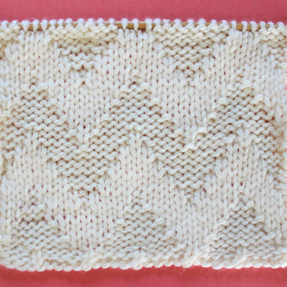 Knitted Wide Chevron Stitch Pattern in white yarn on knitting needle.