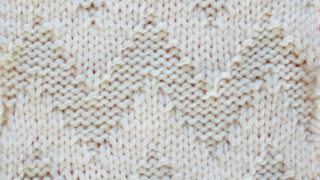 Knitted Wide Chevron Stitch Pattern in white yarn on knitting needle.