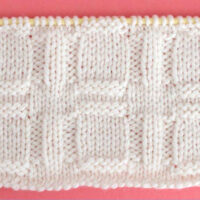 Knitted Window Stitch Pattern in white yarn on knitting needle.