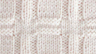 Knitted Window Stitch Pattern in white yarn on knitting needle.