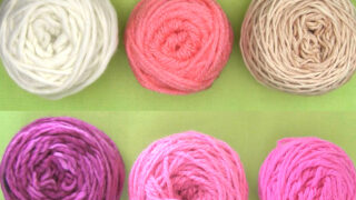 Six yarn balls in purple, pink, and white yarn colors arranged atop a green background.