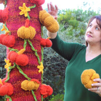 Knitted Pumpkin Tree being crafted by woman while yarnbombing.
