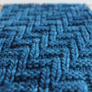 Diagonal Chevron Zigzag Knit Stitch Pattern in blue yarn on knitting needle.