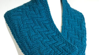 Knitted Scarf in Chevron Zigzag Knit Stitch Pattern texture with blue yarn color on dress form.