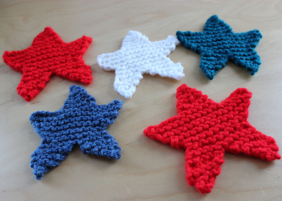 5 knitted star shapes in red, white, and blue yarn colors.