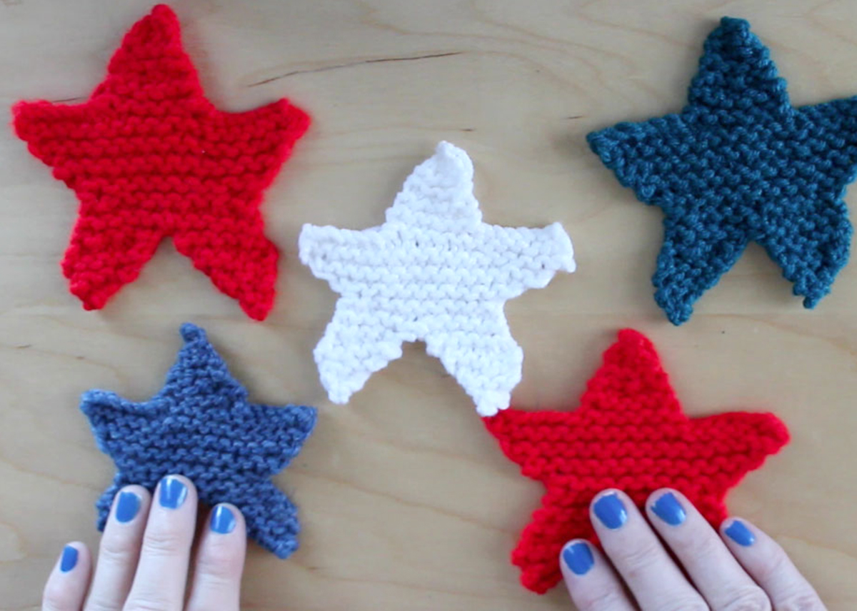 5 knitted star shapes on a tabletop with woman's hands in red, white, and blue yarn colors.