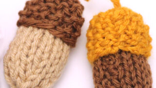 Two knitted acorn softies in brown, yellow, and beige yarn colors on a white background.