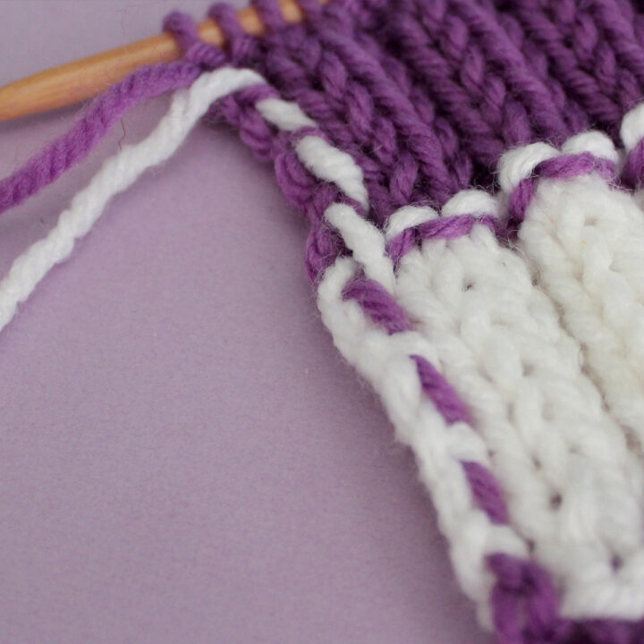 Yarn Carried up the side of a knitted swatch in stripes of purple and white colored yarn.