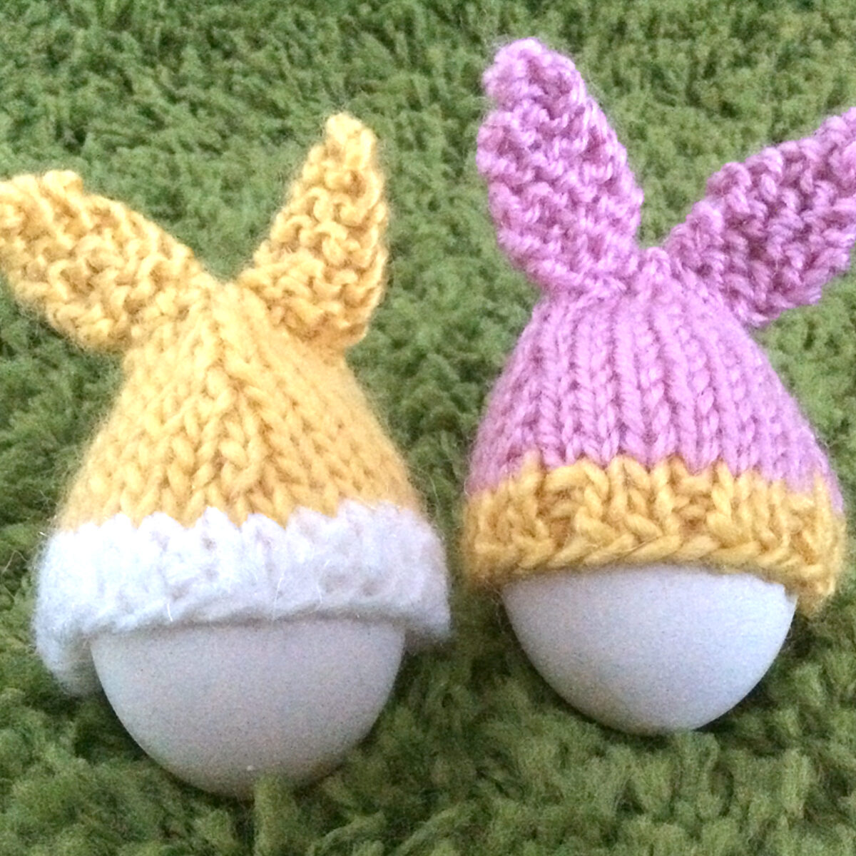 Two eggs with knitted easter bunny rabbit ear toppers as cozies on a green backdrop.