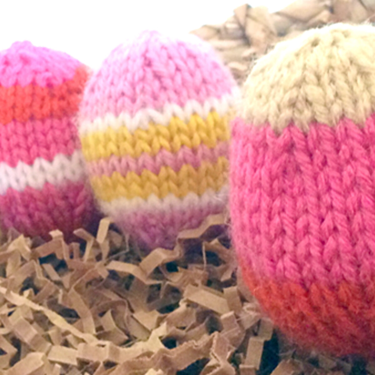 Knitted Easter Egg Softies in yellow and pink yarn colors.