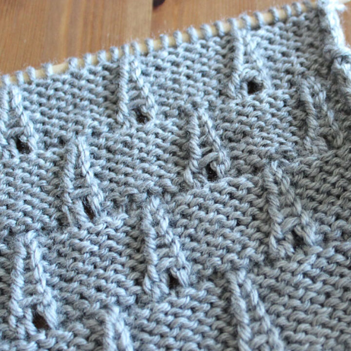 Eiffel Tower Eyelet Stitch Knitting Pattern texture in gray color yarn on knitting needle.