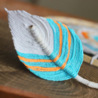 Fiber Feather created with yarn in blue, orange, and white colors.