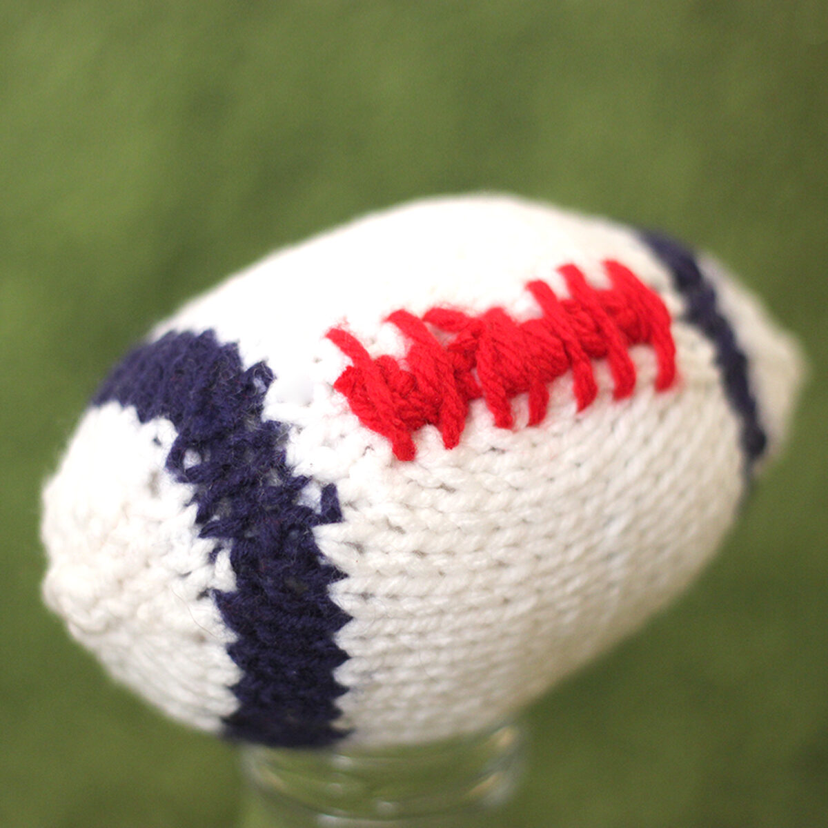 Knitted Football softie toy in white, blue, and red yarn colors.
