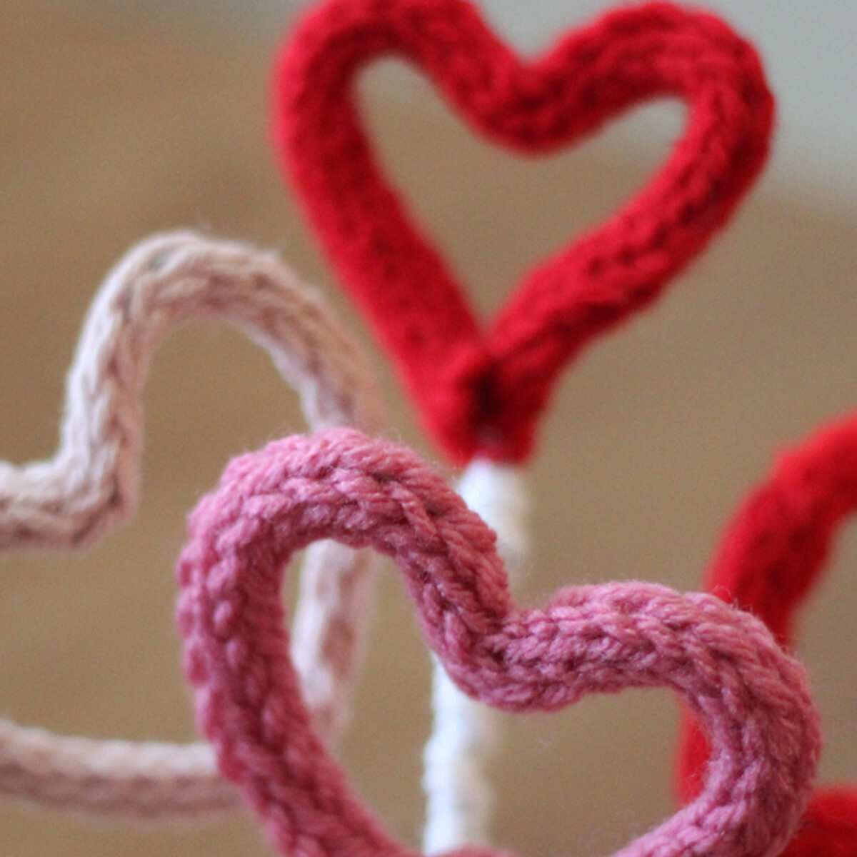 Knitted heart shaped i-cords in pink, red, and white yarn colors.