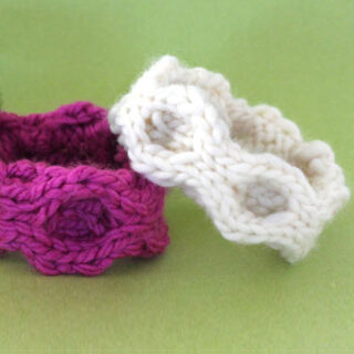 Knitted bracelets in honeycomb stitch texture with pink and white yarn colors atop a green background.