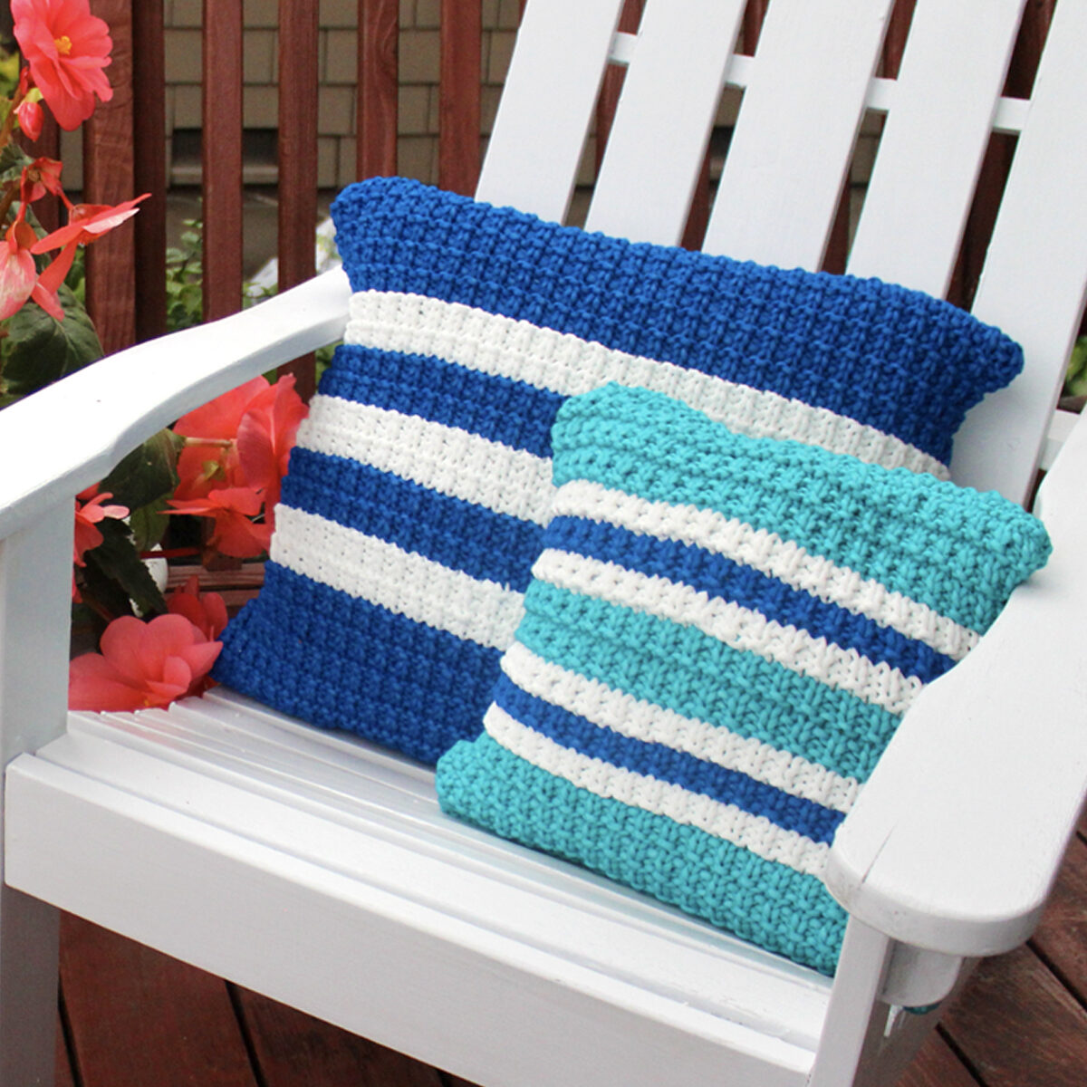 Two knitted pillows in hurdle stitch texture in shades of blue yarn color on a white adirondack chair.