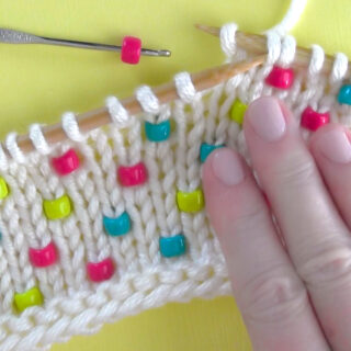 Knitted swatch in white yarn with beads inserted vertically and hand.