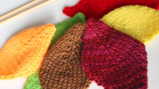 Knitted Leaf shapes in brown, green, yellow, and red colored yarn.