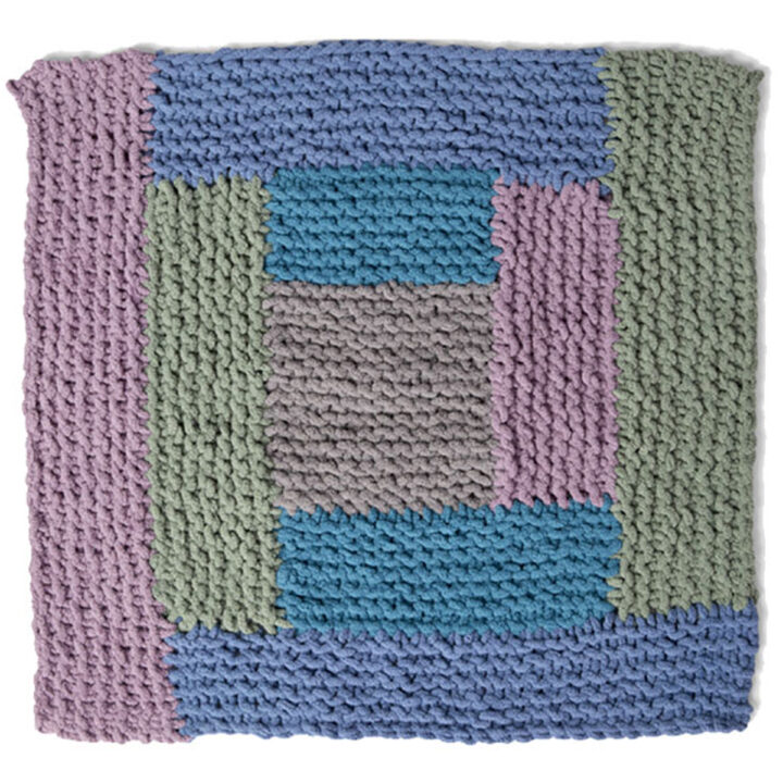 Knitted Square in the Log Cabin Design with shades of blue, green, and purple yarn colors.