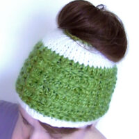 Woman wearing knitted Messy Bun Hat in green and white colored yarn with hair piled atop head.