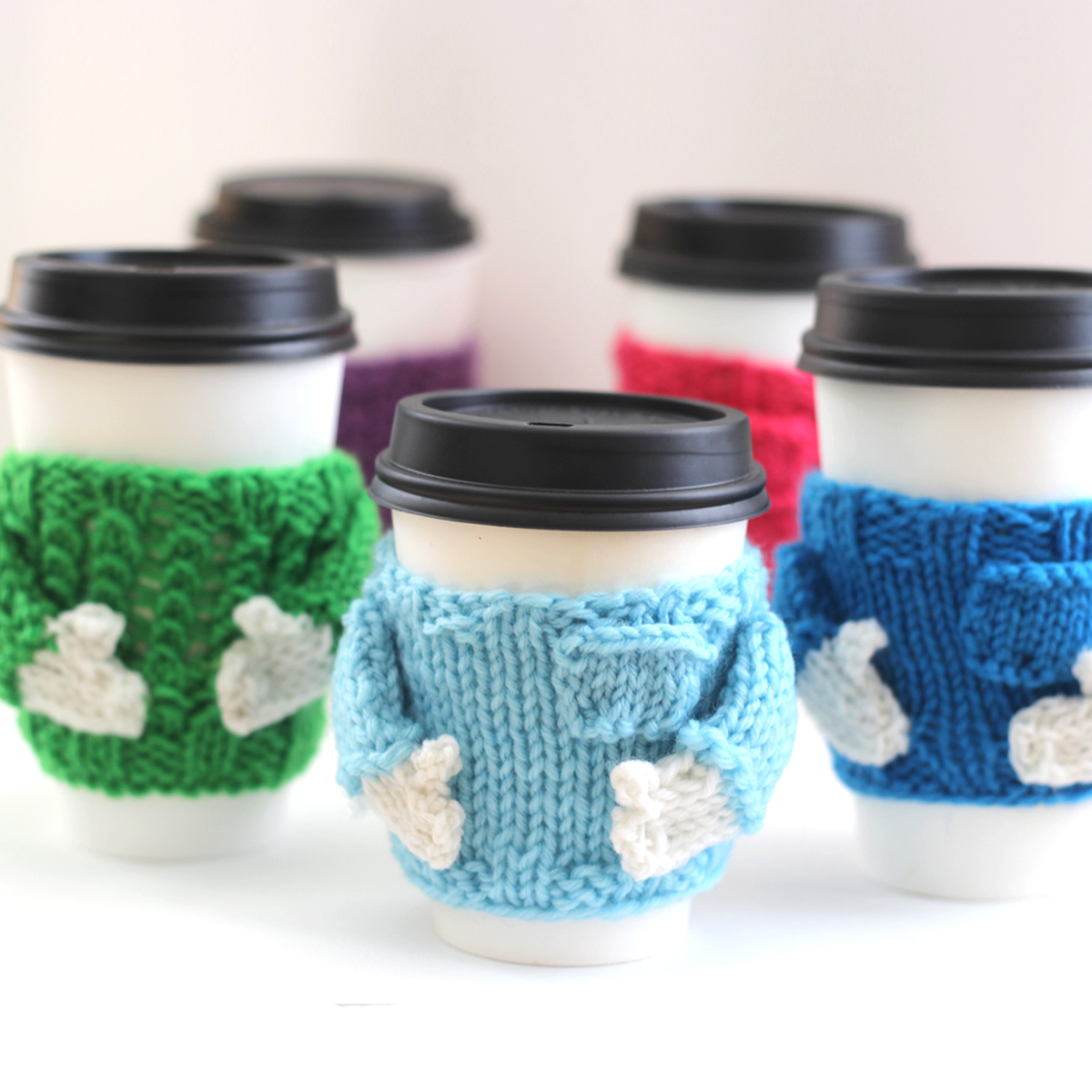Take Out Coffee Cups with knitted sweater designed mug cozies in various colors.