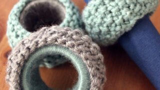 Knitted napkin rings in blue and grey yarn colors.