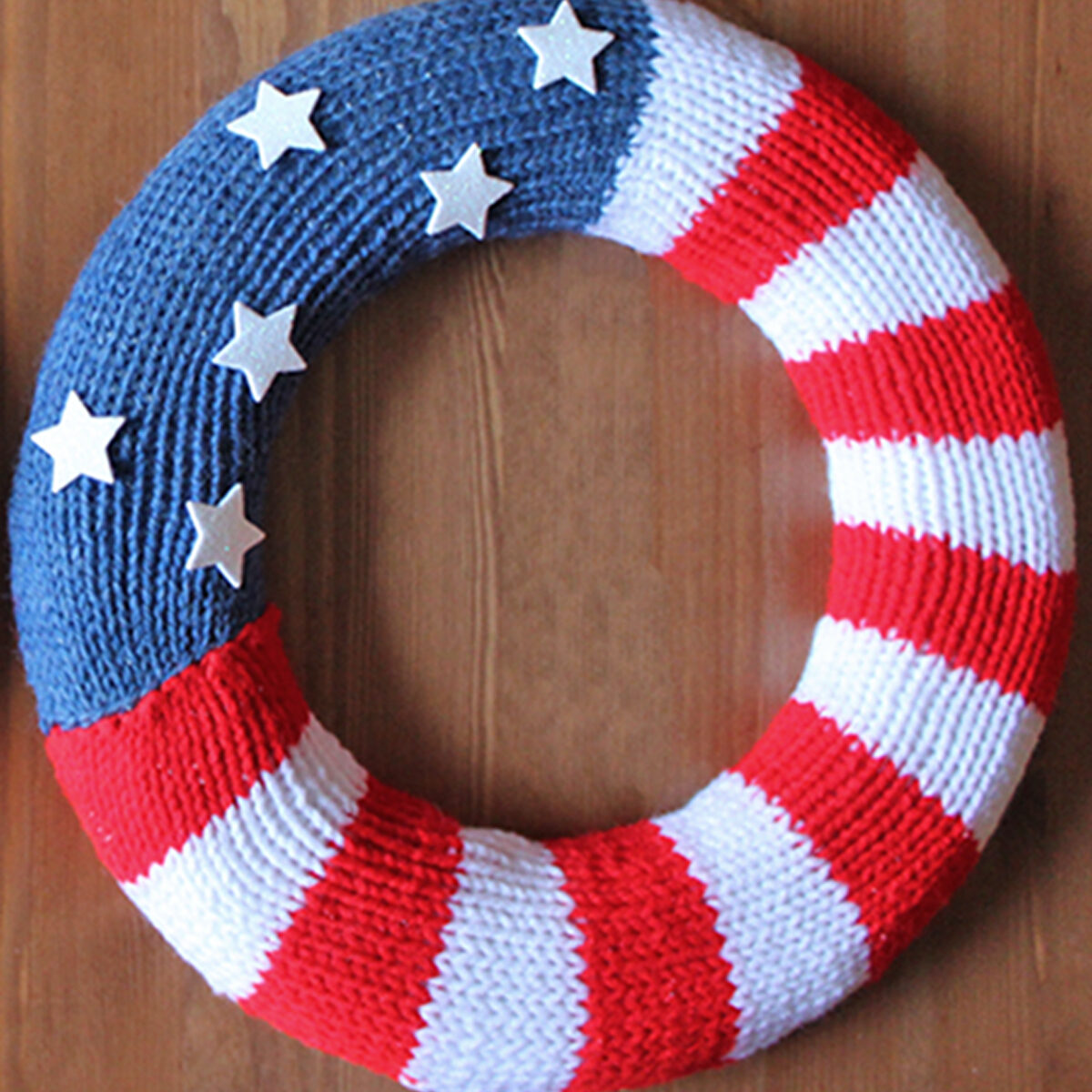 Knitted wreath in american flag design with red, white, and blue yarn colors.