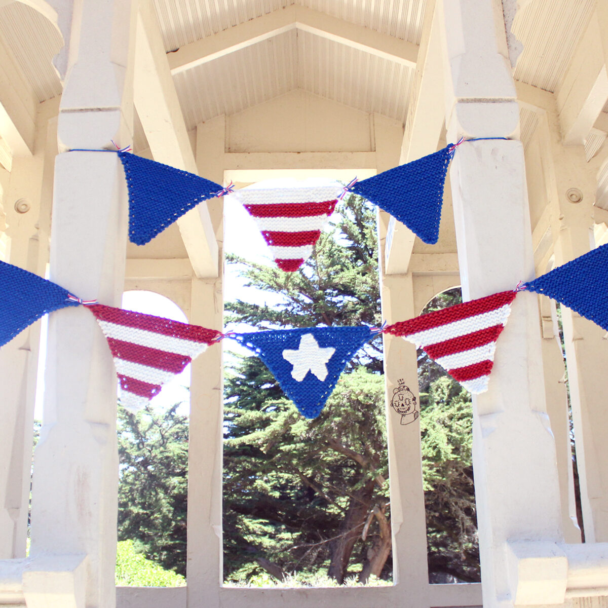 Knitted pennant banner in patriotic USA colors of red, white, and blue strung within a white gazebo.
