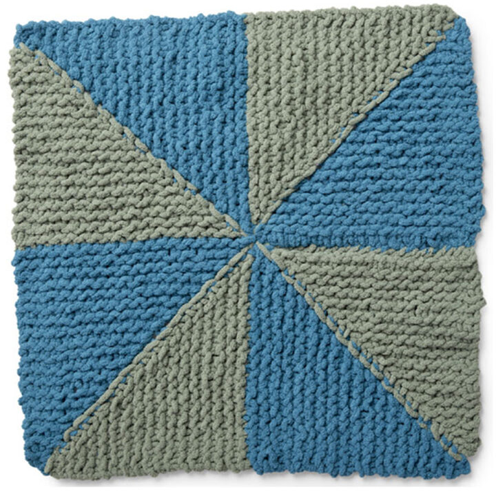 Knitted Square in the Pinwheel Design with blue and green yarn colors.