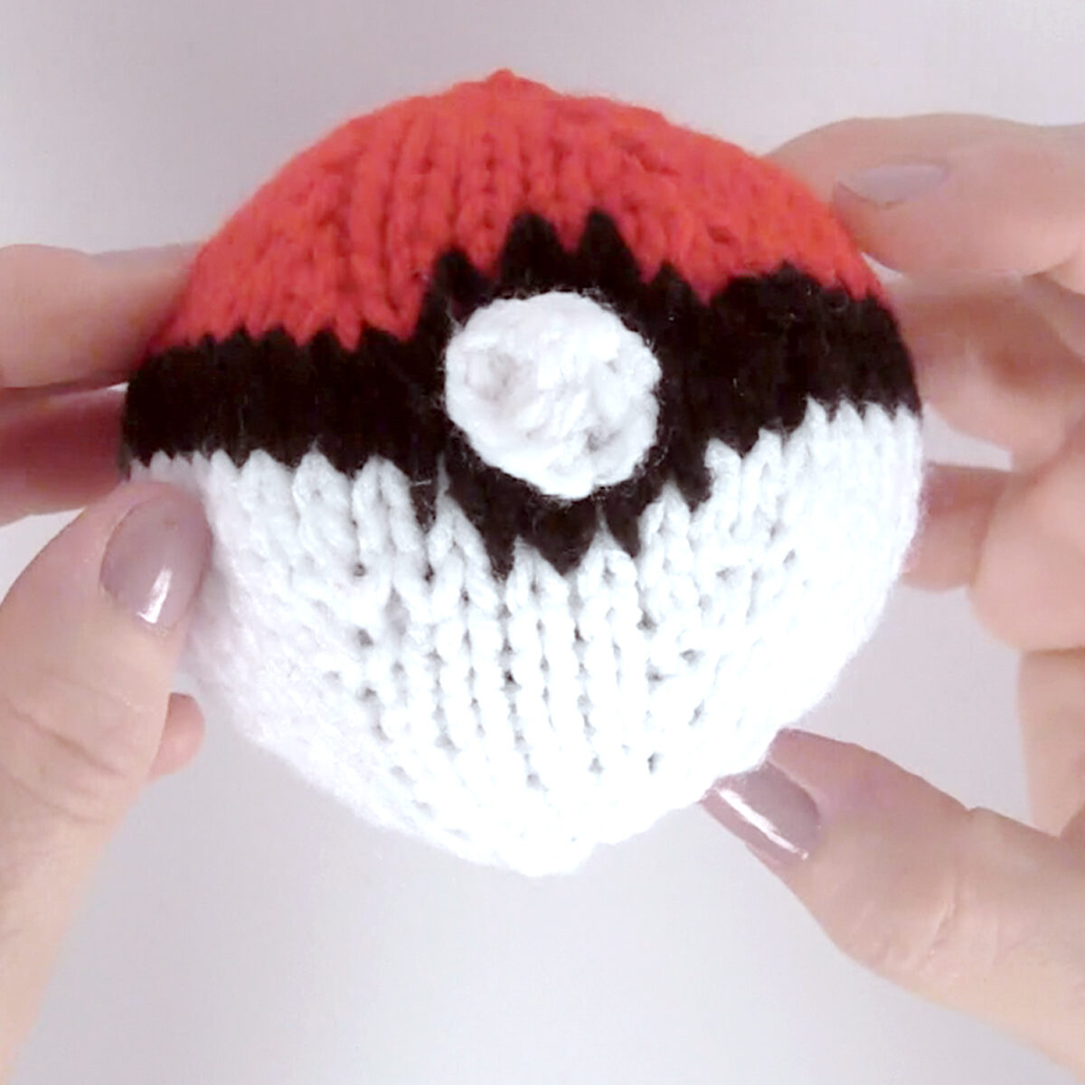 Knitted Poke Ball in white, red, and black yarn colors held by two hands.