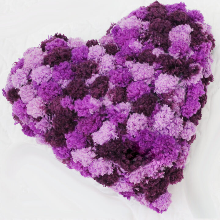 Knitted heart shaped pillow in pom pom yarn in shades of purple yarn color.