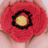 Knitted Poppy Flower in red color yarn held by two hands.