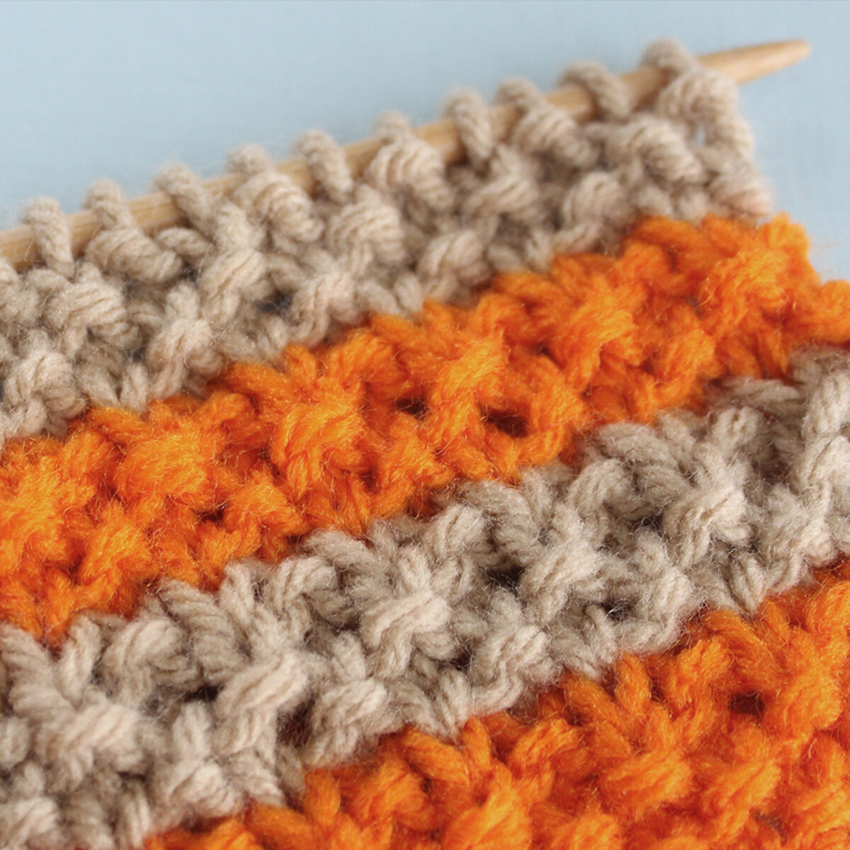 Right side of knitted swatch in tan and orange color yarn.