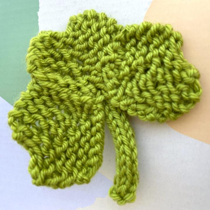 Knitted Shamrock Clover Shape in green color yarn.
