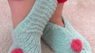 Knitted slippers in light blue yarn color with pink pom poms.