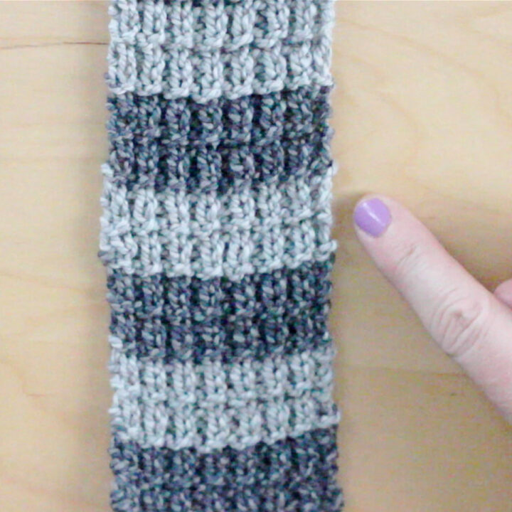Knitted swatch in gray colored horizontal stripes with woman's hand.