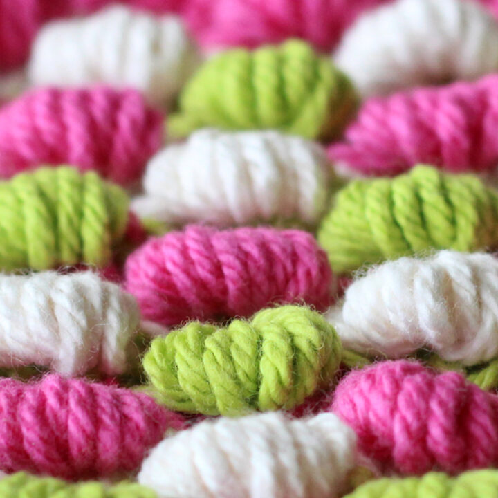 Spring Bobble Stitch Knitting Pattern texture in alternating green, pink, and white colors of yarn.
