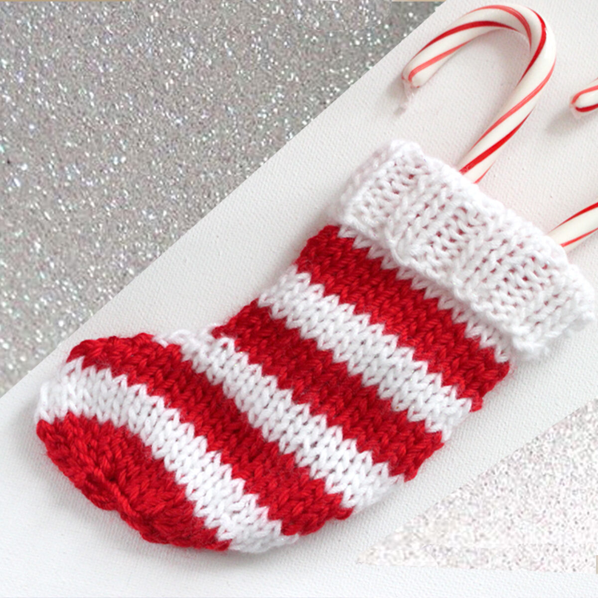 Knitted mini Christmas Stocking in alternating horizontal stripes in red and white yarn with candy canes inside.