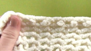 Hand holding a swatch of knitting to demonstrate the stretchy bind off technique.