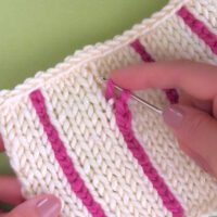 Hand holding crochet hook to add vertical stripe in pink yarn with knitted swatch in stockinette stitch in white yarn color.