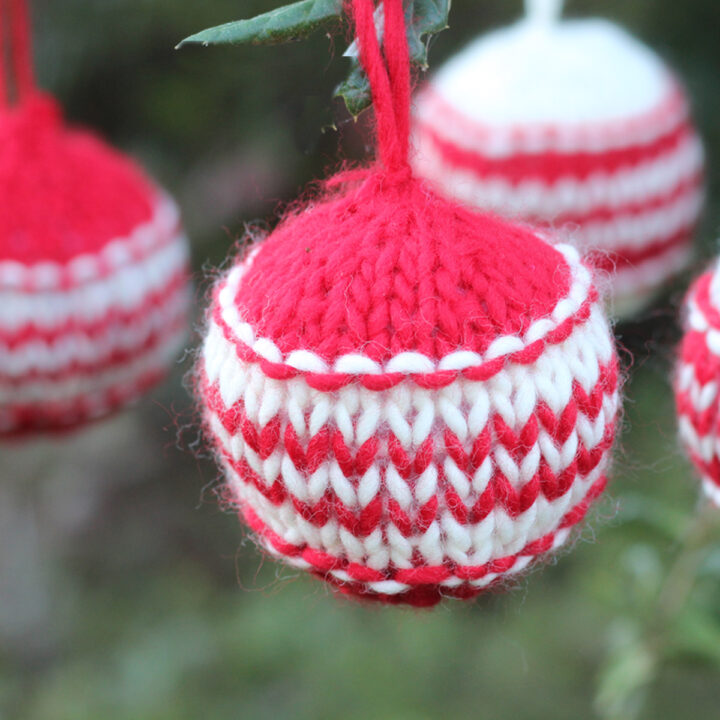 Knitted Christmas Ball Ornaments in red and white yarn colors hanging from outdoor greenery branches.