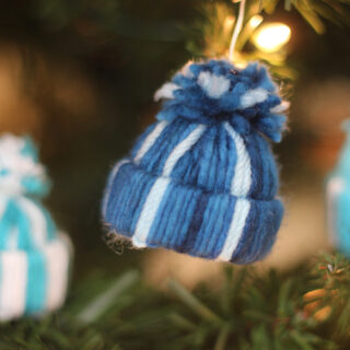 Yarn Hat holiday ornament in blue and white stripes hanging with Christmas tree.
