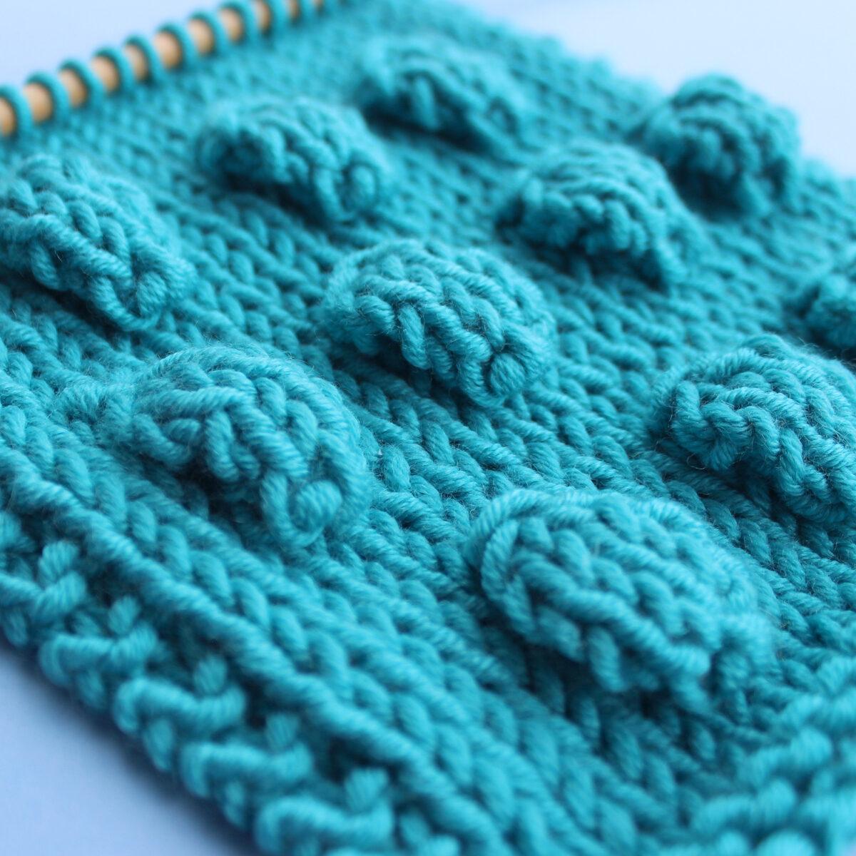 Bočni kut Bobbles u Stockinette Stitch na igli za pletenje u pređi plave boje.