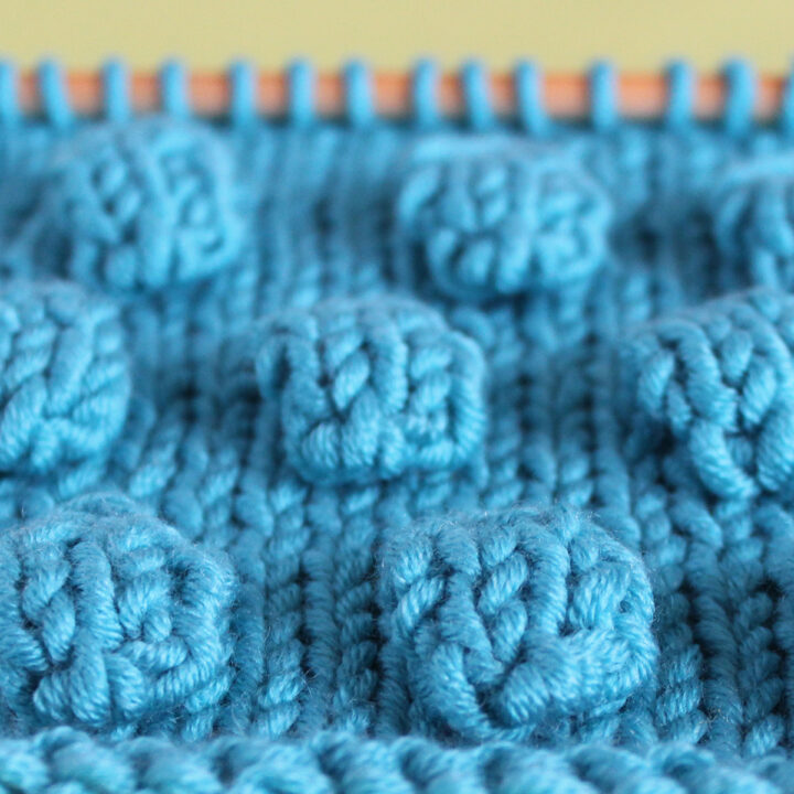 Bobbles in Stockinette Stitch on knitting needle in blue color yarn.