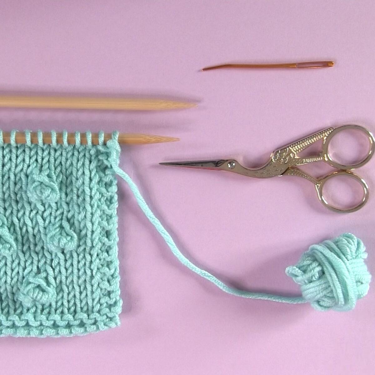 Materijali za pletenje uzorkom Bobble Stitch u svijetloplavoj boji pređe, igle za pletenje, škare i iglu za tapiserije.