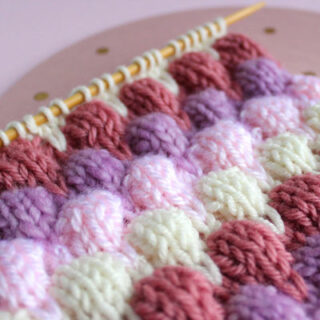 Knitted bubble stitch pattern in colorful pink and purple yarn colors.