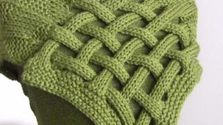 Celtic Saxon Scarf knitted in green yarn on mannequin torso.