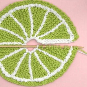 Knitted dishcloth in fruit slice design with green yarn on needle.