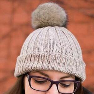 Knitted rib hat in grey yarn with pom pom on girl's head.
