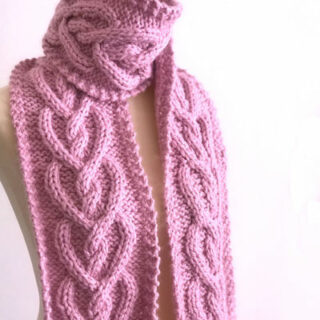 Cable Heart knitted scarf in pink yarn on mannequin torso.